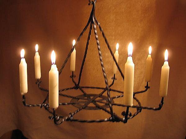 """Tordierter Kronleuchter mit 8 Armen und feuerverschweißten Kerzenhaltern wie auch Leuchterhalter. Der Leuchter besitzt acht Arme, die auf einem Blechring fixiert sind (durch Nieten) und an einem tordierten Metallreifen mit Draht """"festgebunden"""" sind. Die einzelnen Leuchterarme wurden mit Kleinen Blechstreifen feuerverschweißt die kleine """"öhrchen"""" bilden, damit eine Kerze vernünfig halt auf dem Leuchter hat. Die Halterung des Ganzen Leuchters besteht auch aus 4 tordierten Metallstäben (in diesem Fall Stahl) die oben miteinander Feuerverschweißt sind und im unteren Bereich Haken bilden, die den Leuchter halten."""