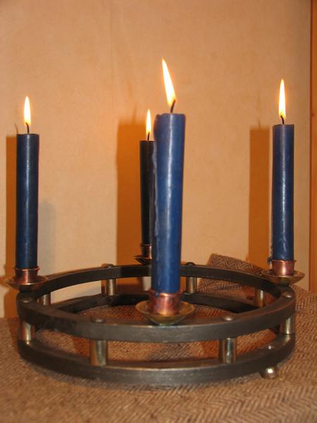 Adventsleuchter: Dieser Leuchter besteht aus 2 Massiven Stahlringen (feuergeschweißt) die mit Nieten miteinander verbunden sind. Als Distanzen dienen Buchsen aus Schmiedemessing. Die Füße sind wiederum auch aus Schmiedemessing geschmiedet. Die Kerzenhalter bestehen aus Messing / Kupfer und wurden auf den oberen Ring vernietet.
