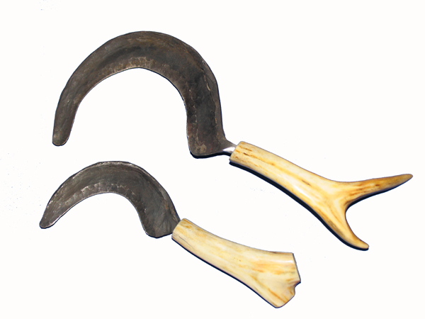 """Beide Sicheln wurden von Hand geschmiedet und scharf gedengelt. Sie bestehen aus einem C45 Stahl und wurden mit einem Hirschgeweihgriff (poliert) versehen. Die kleinere der Sicheln hat einen """"Durchmesser"""" von 12 cm."""